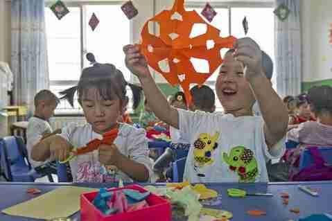 幼儿园的小朋友吕宸逸向同学们展示自己的剪纸作品