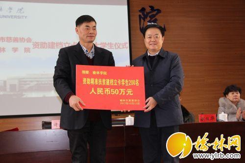 市慈善协会会长刘洪(右)向榆林学院递交捐赠牌