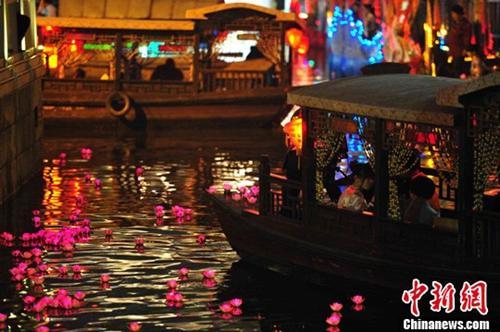 资料图:清明节当晚,广州市民放下两千余盏河灯,表达追思。a href=